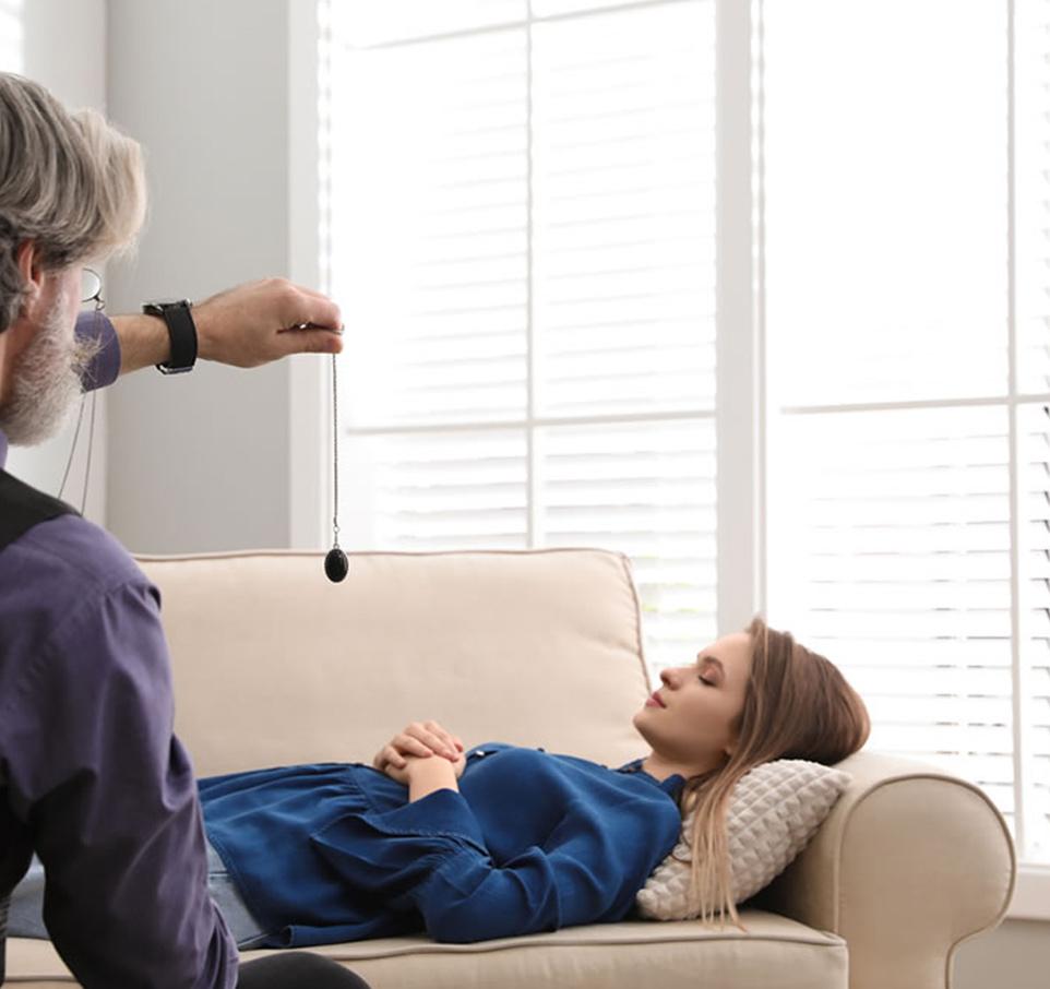 Séance d'hypnose d'une femme allongée sur une canapé beige